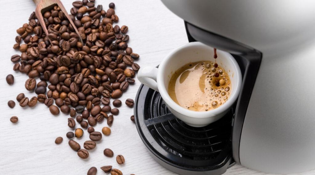 Cup of coffee being brewed by a Keurig coffee maker.