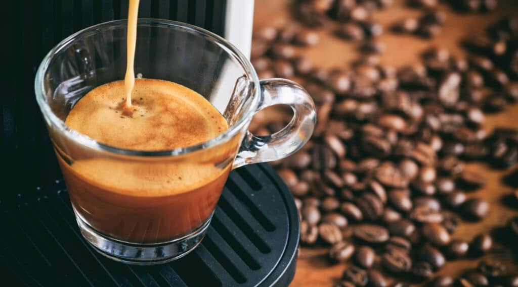 Nespresso machine brewing espresso in a cup.