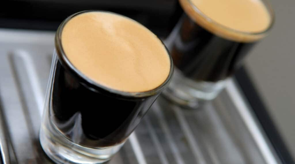 Two glasses of espresso brewed using the Nespresso VertuoPlus and Evoluo models.