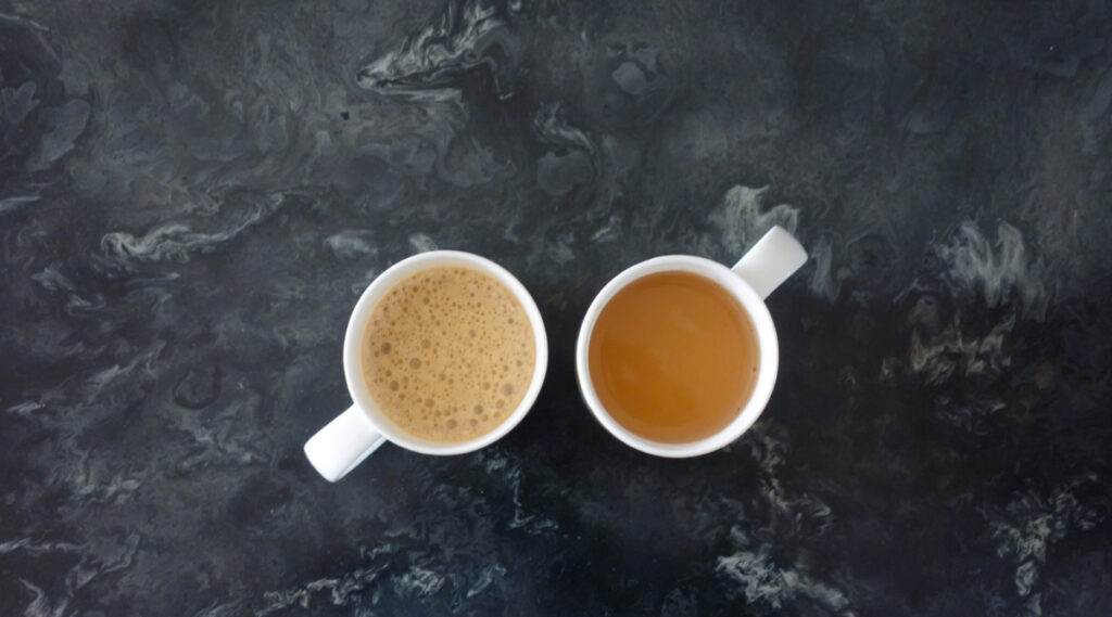 Two coffee cups side by side. One is filled with Espresso and the other filled with coffee.