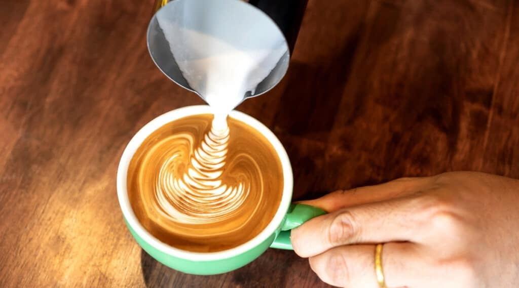 Coffee creamer being poured into a cup of coffee.