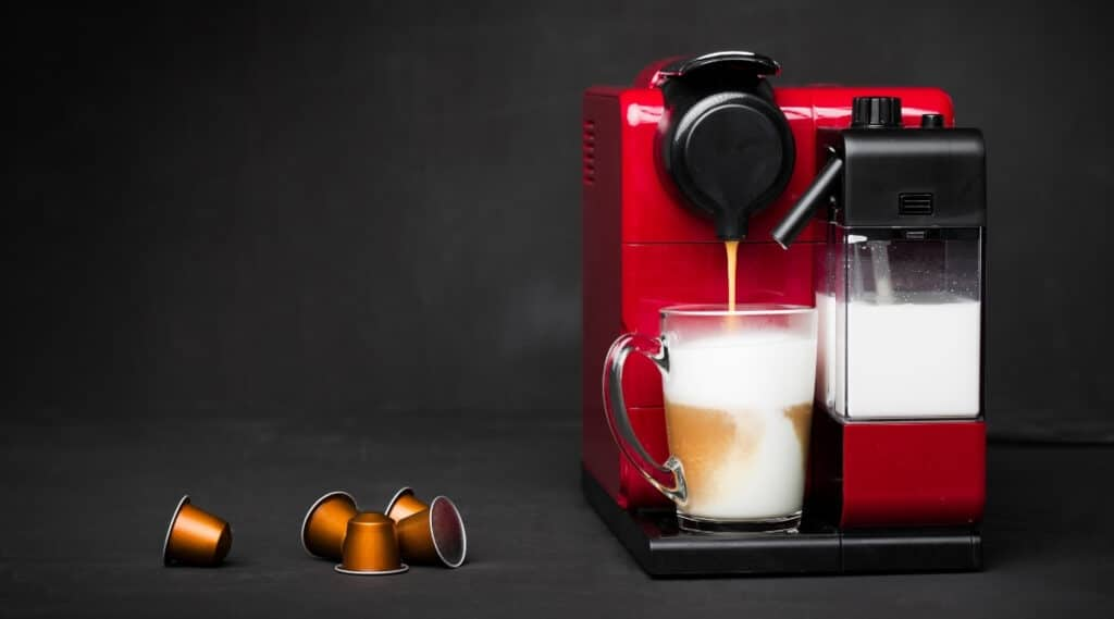 A Nespresso machine brewing a frothy cappuccino.