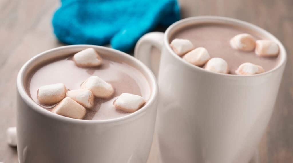 A cup of hot chocolate next to a cup of hot cocoa.