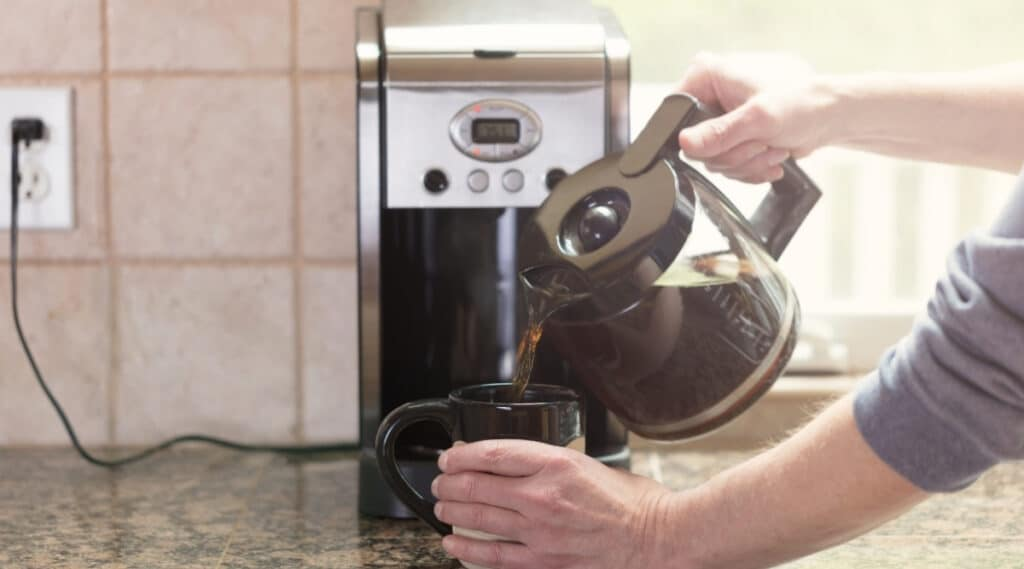 Drip coffee maker brewing coffee into a carafe.