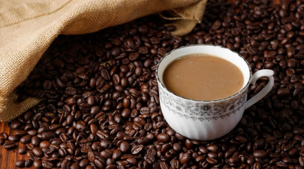 A cup of coffee sitting on top of arabica coffee beans.