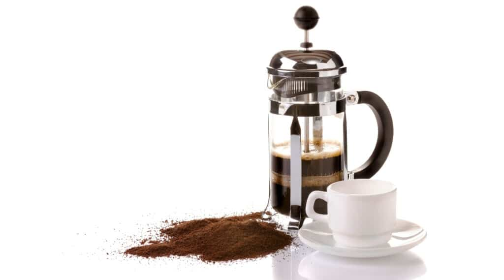 French press using coffee grinds to make a cup of coffee.