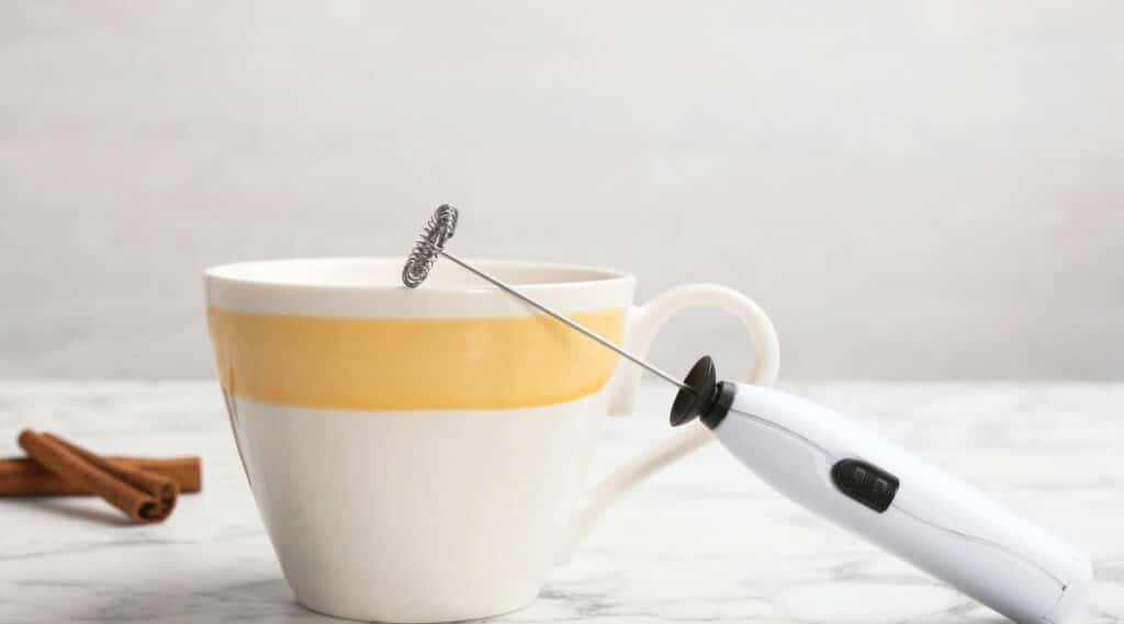 Milk frother resting on a cup of coffee ready to use.